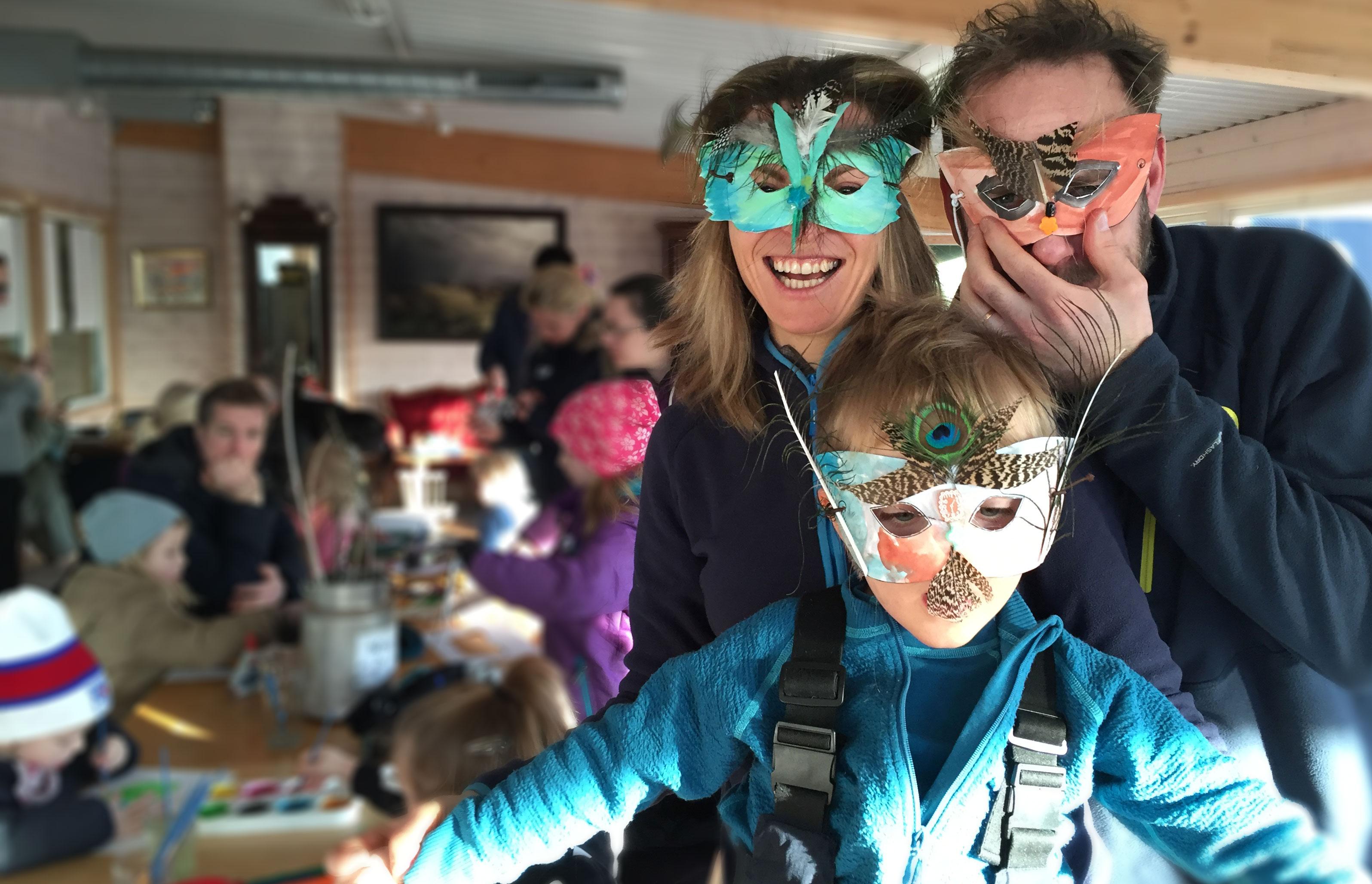 Familie med masker av fjær